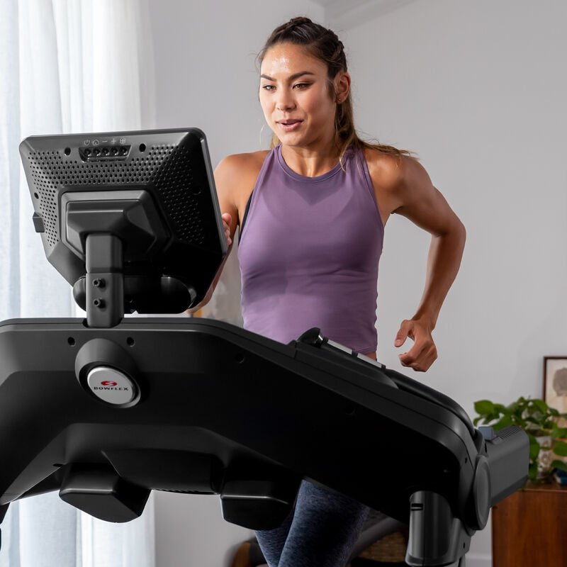 A woman running on a treadmill 10. - mobile expanded view