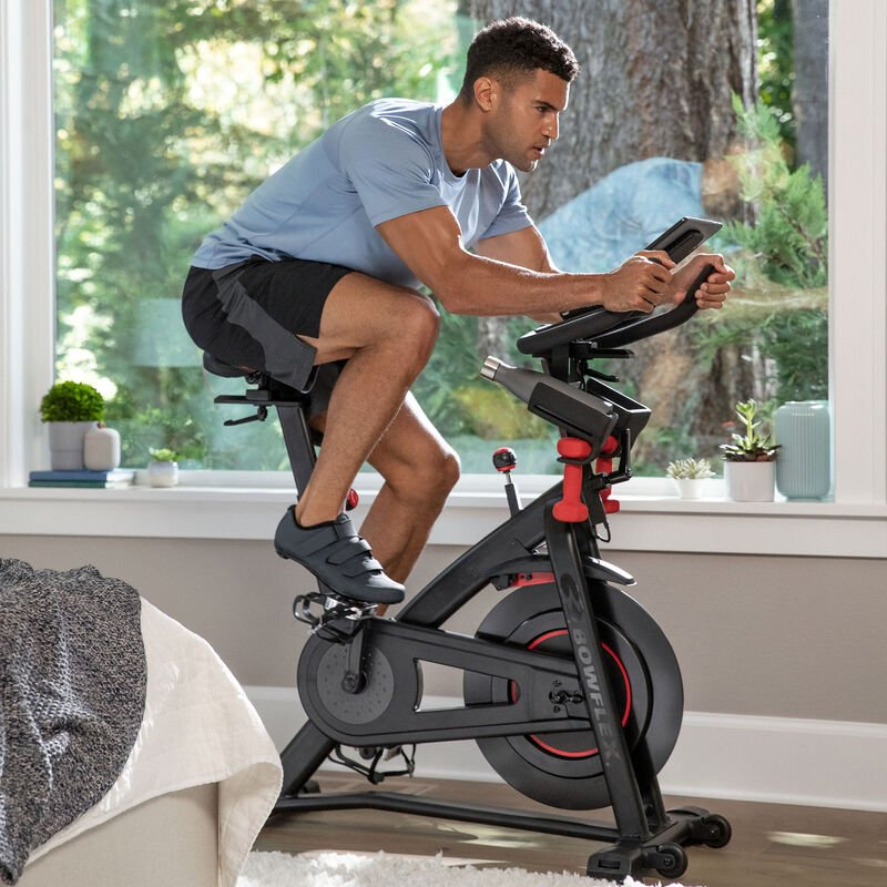 Man riding a stationary Bowflex C6 exercise bike - expanded view