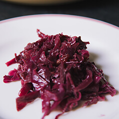 Braised cranberry and cabbage on a white plate.