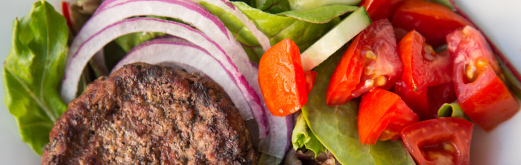 Deconstructed Burger Salad Recipe. A hamburger patty on top of vegetables and drizzled with a creamy chipotle sauce.