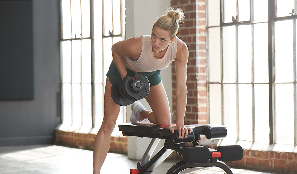 a woman performing a dumbbell row.