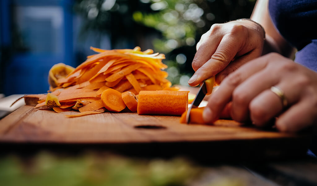 A person cutting carrots.