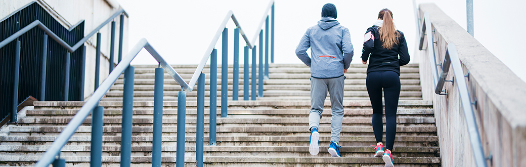 Two fit people jogging outside up stairs. Self Care in 2018: Three Simple Tips