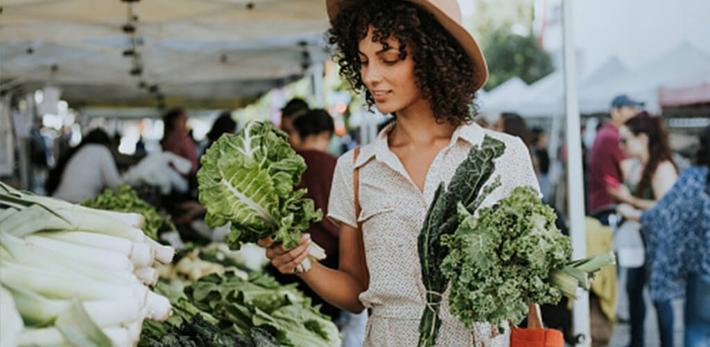 A woman holding leafy greens at an outdoor market.