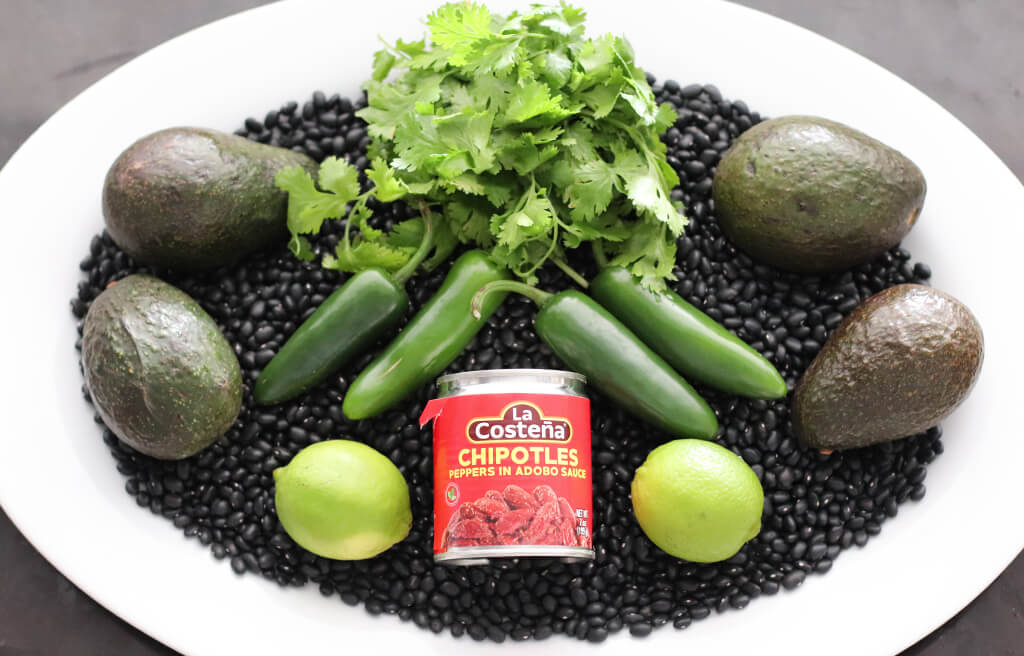 avocados, cilantro, black beans, and peppers on a plate.