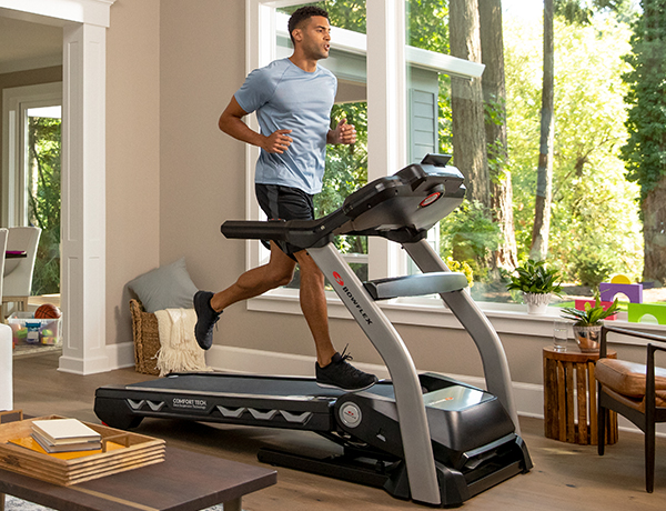 man running on a BXT216 Treadmill in a sunny room