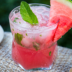 A glass filled with watermelon mojito mocktail. Garnished with mint and watermelon on a table at the coast.