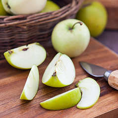 Green apples slices on a wood cutting board.