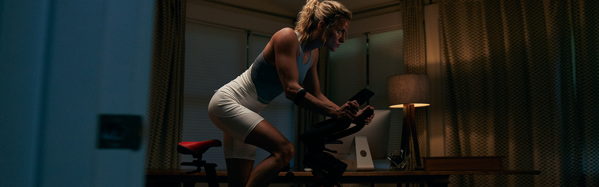 A fit woman using the C6 bike in her home.