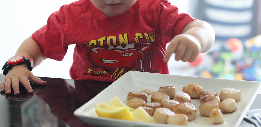 a child eating seared scallops