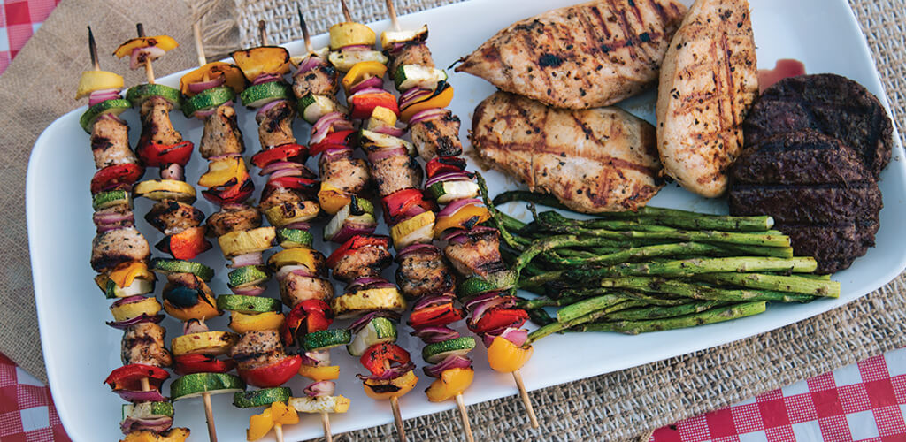 A plate of chicken and veggie kabobs next to grilled chicken, burgers, and asparagus.