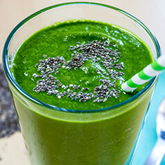 close up image of a peachy green smoothie in a glass with a straw.