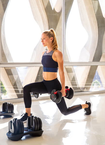 A fit woman performing a weighted front lunge using Bowflex SelectTech Dumbbells.