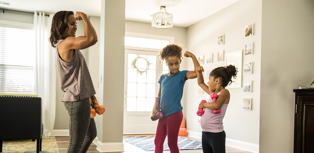 A woman and two children flexing their biceps.