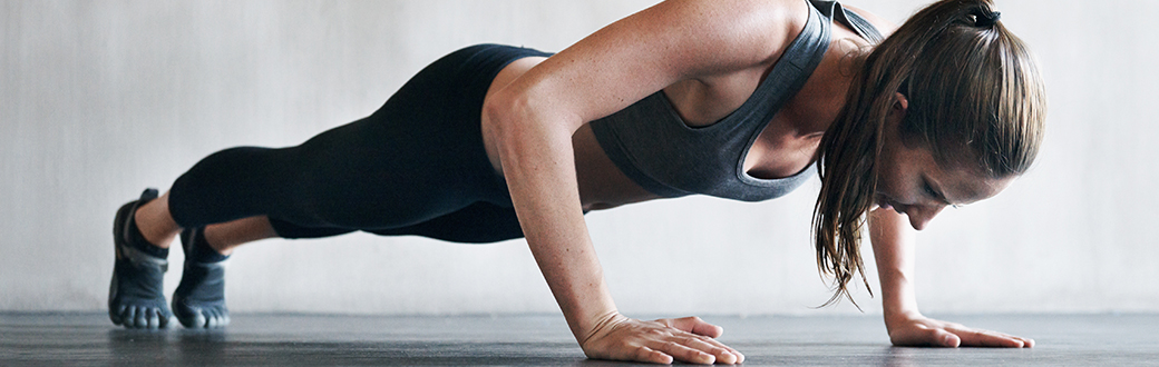 A fit woman performing a push-up. Push-Up Workout Guide: The Best Push-Up Exercises