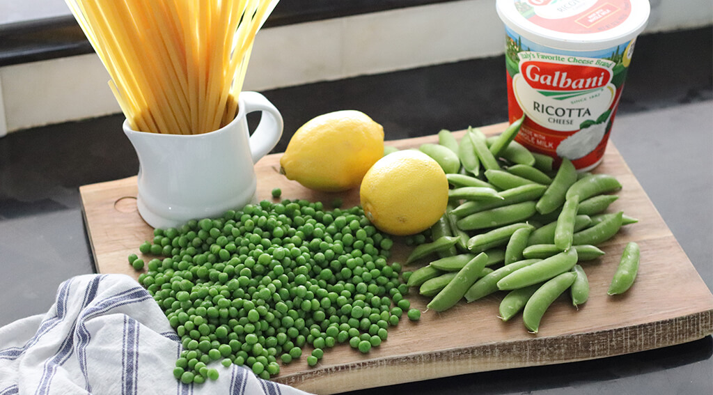 uncooked fettuccine, lemons, peas, snap peas, and ricotta on a cutting board.