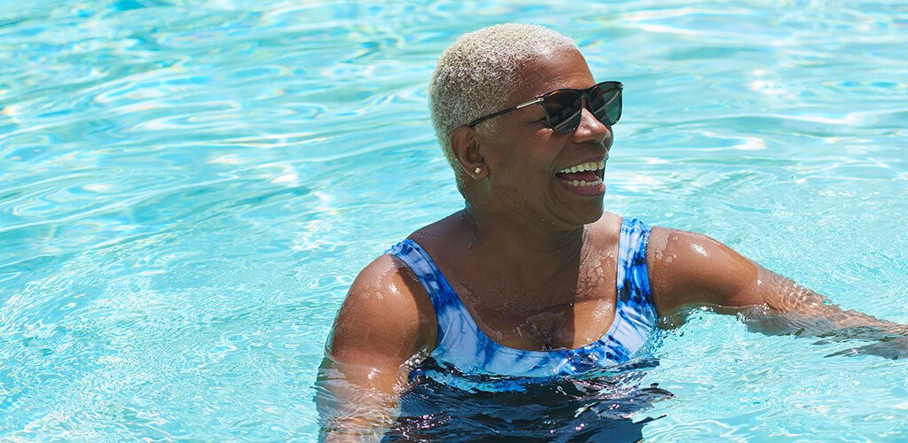 A woman smiling in a pool.