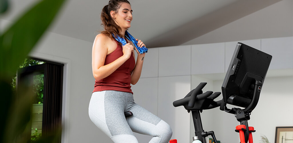 A woman using a Bowflex Velocore Indoor Cycling Bike.