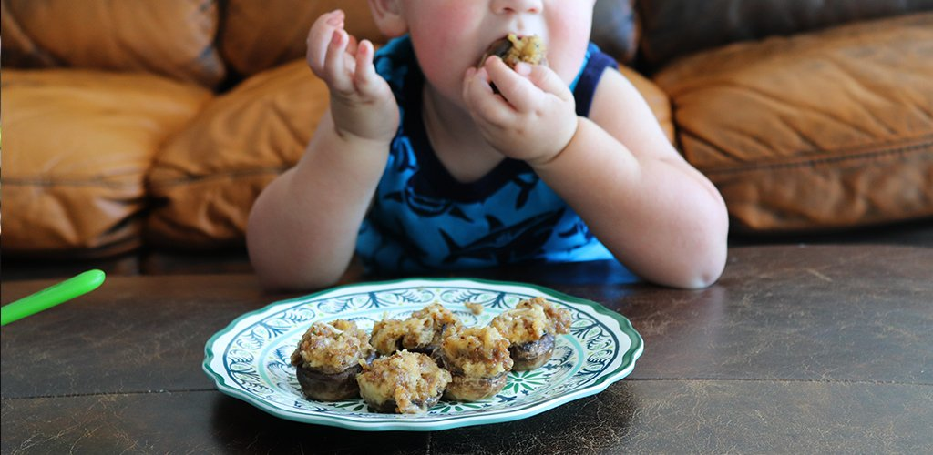 a toddler eating stuffed mushrooms