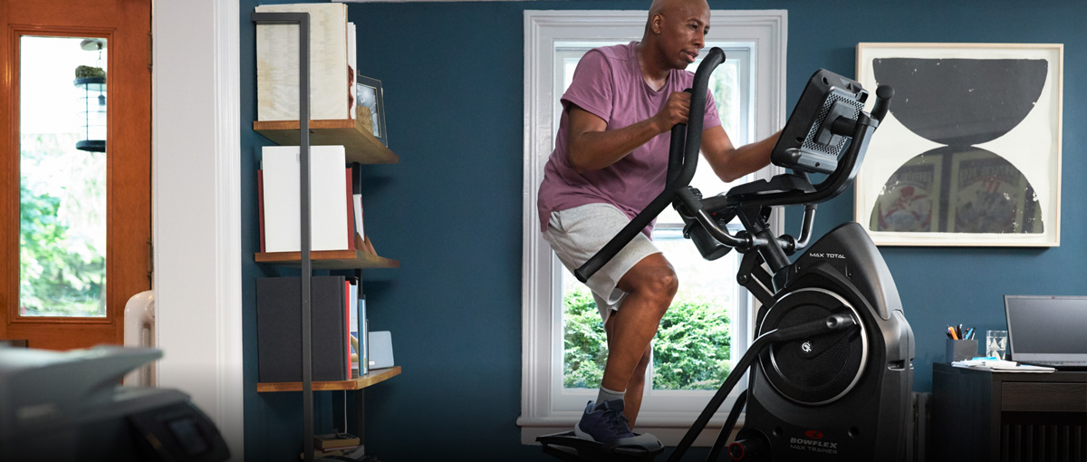 Man exercising on a Max Trainer from his home office