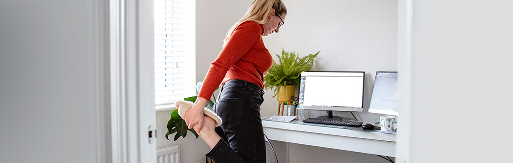 A woman stretching in her home office.