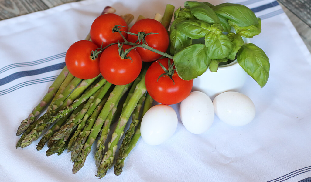 asparagus, tomatoes, basil, and eggs on a counter.