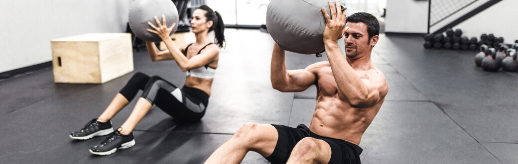 Two fit people in a gym performing one of the best abs workout with a medicine ball. Ab Workout Guide – Ab-solutely the Best Ab Exercises.