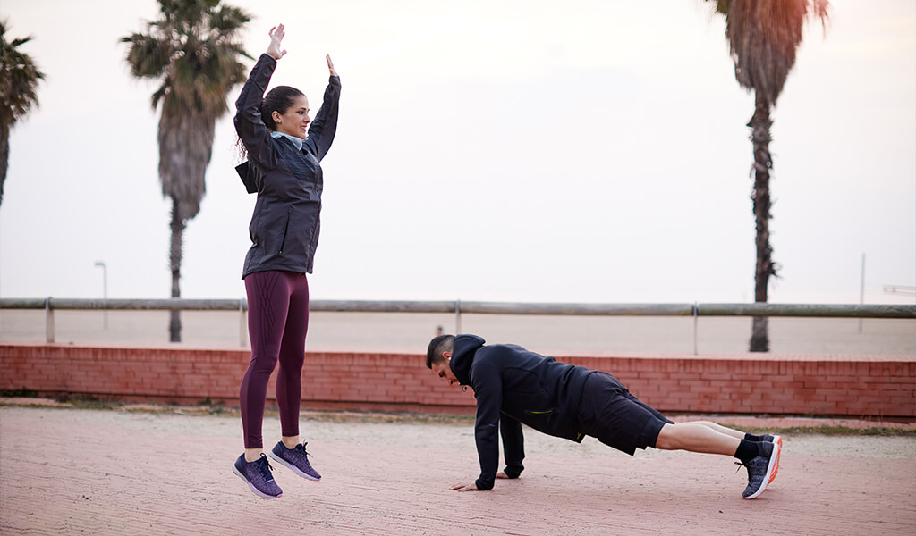 A woman and man doing bodyweight exercises outside.