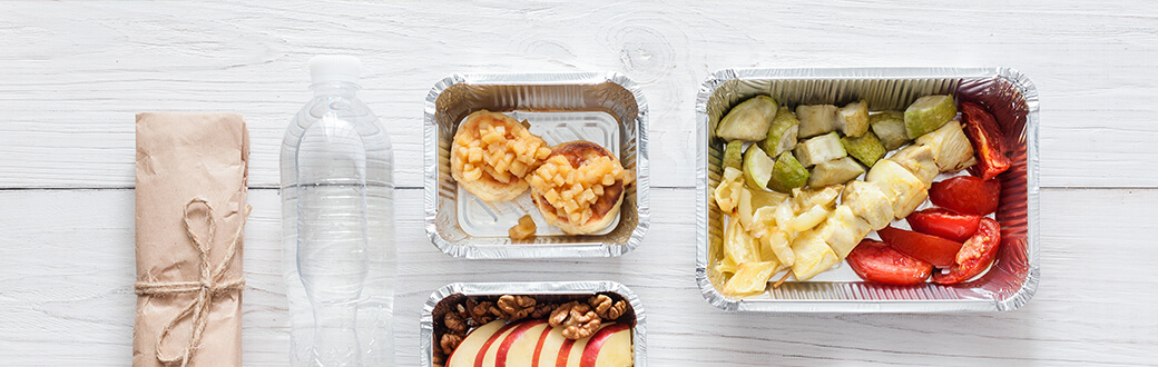 Camping dinner ideas in foil containers on a table.