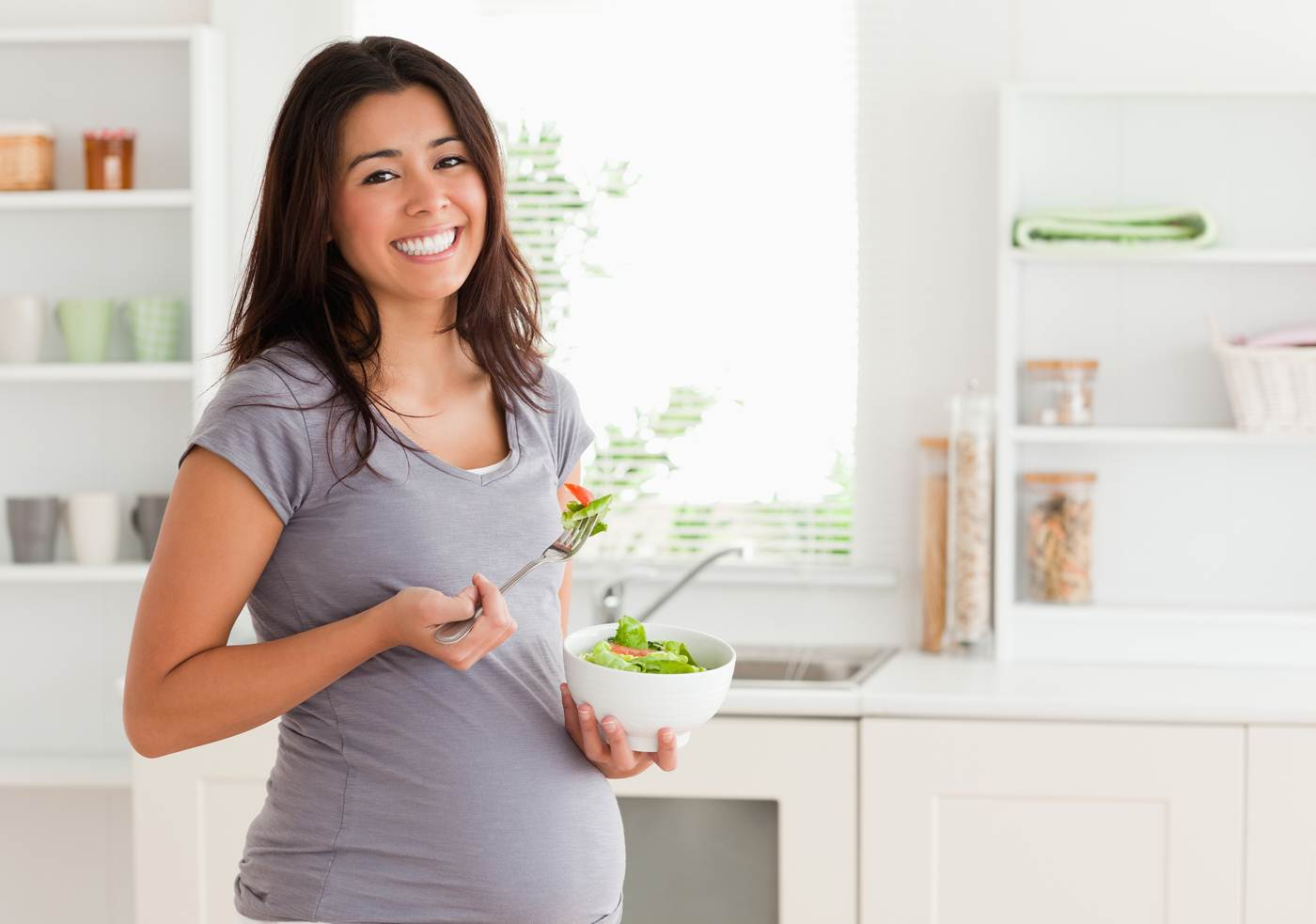happy pregnant woman eating a salad