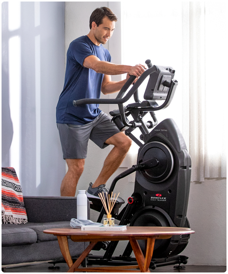 Man in his living room working out on a Max Total elliptical trainer