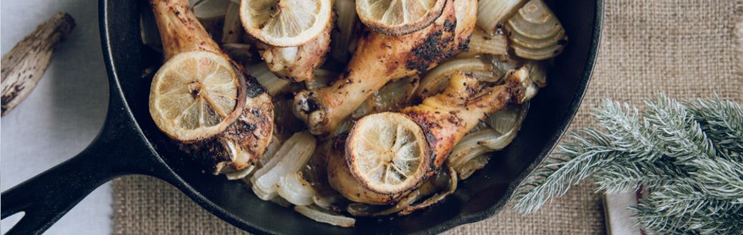Roasted chicken legs topped with lemon slices in a cast iron skillet