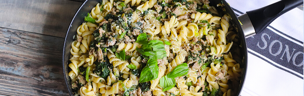 Kale and sausage pasta in a skillet.