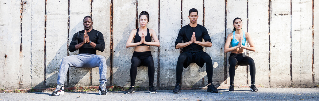 Four people performing wall sits.