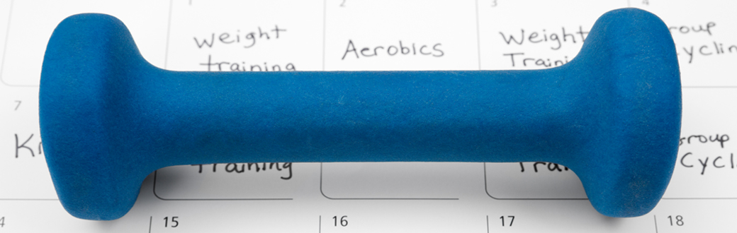 A dumbbell sitting on a workout calendar.