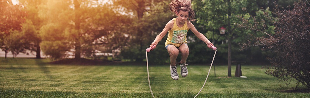Child jumping rope outside
