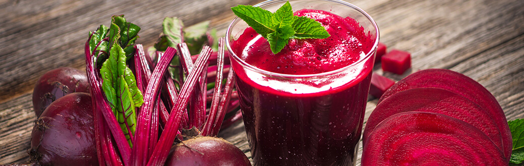 A glass of beetroot juice surrounded by beets.
