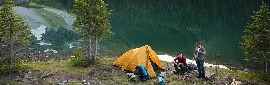 Two people camping next to a lake.