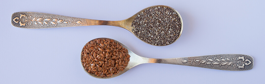 A spoonful of chia seeds next to a spoonful of flax seeds.