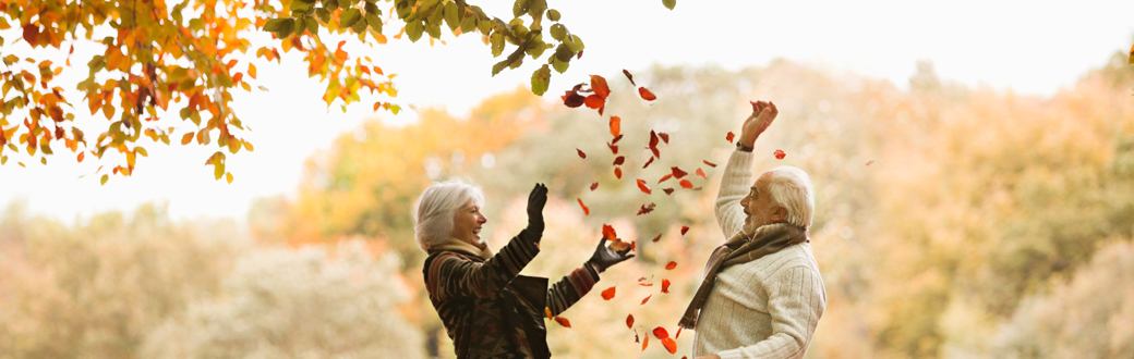 Two older people in warm clothes throwing leaves in the air.