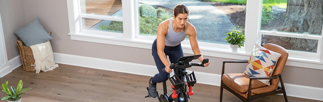 A woman using a Bowflex Indoor Cycling Bike.