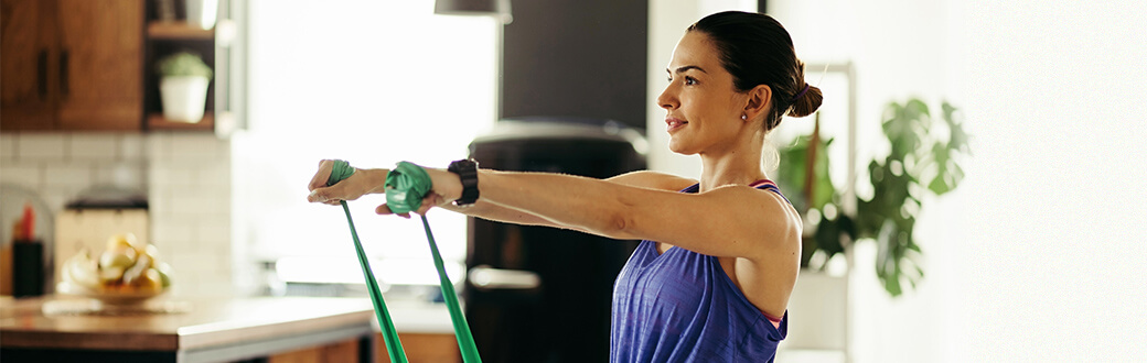 A woman performing a resistance band front raise.