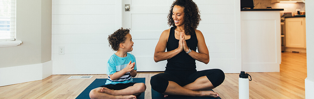 A woman and a child doing yoga.