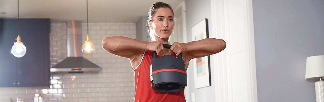 A woman using a Bowflex SelectTech 840 Kettlebell