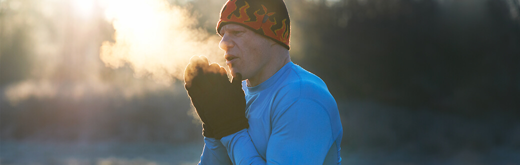 A man outdoors, in workout clothes looking cold.