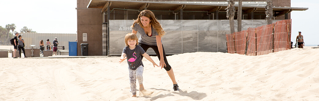 A woman playing with a child in the sand. Improve the way you move with Bowflex LateralX Trainer.
