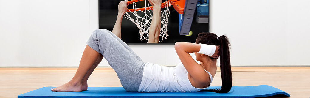 A woman performing a crunch while watching college basketball.