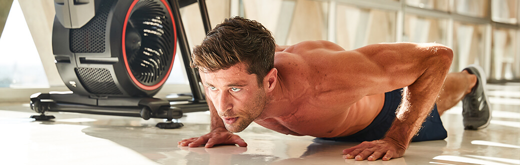 A fit man performing a push up.