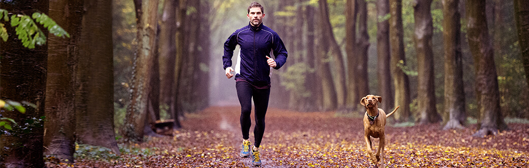 A fit man running outside on fallen leaves with a dog.