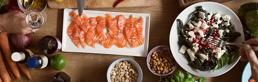 Salmon, nuts, and a salad on a table.